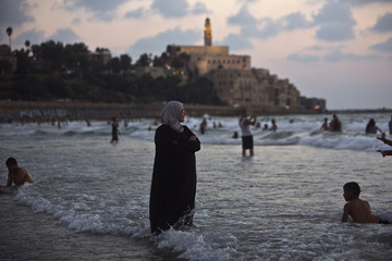Palestinian woman from Ramallah stands in the water of the Mediterranean sea at a beach in Tel Aviv where Jaffa is seen in background, during Eid al-Fitr