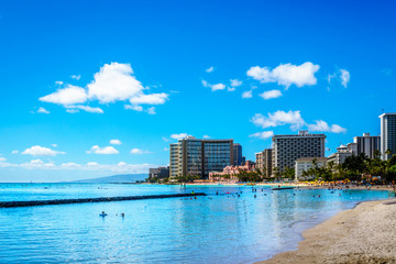 Waikiki Beach, with its many resorts under blue sky and white sand, makes it one of the world's most famous beaches. Located in Honolulu on the Hawaiian island of Oahu