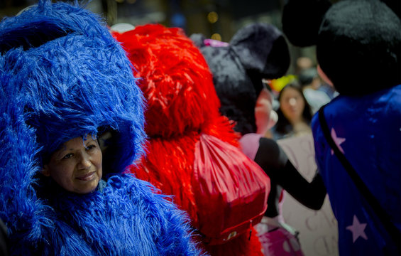 A woman dressed as the Sesame Street character Cookie Monster looks out from under her costume following a rally in support of organizing costumed characters in New York's Times Square