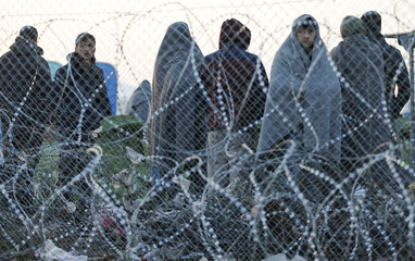 Migrants stand behind a border fence at the Greek-Macedonian border
