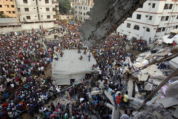 Rescue workers try to rescue trapped garment workers in the Rana Plaza building which collapsed, in Savar