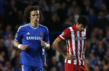 Chelsea's Luiz walks past Atletico Madrid's Costa after Chelsea scored the first goal for the team during their Champions League semi-final second leg soccer match at Stamford Bridge Stadium in London