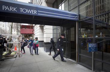 A New York Police Department officer walks into the South Park Tower rental apartment past pedestrians in Manhattan, New York