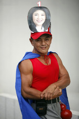 Bodybuilder wearing picture of Yingluck Shinawatra, poses for photo as supporters of her Puea Thai party gather for last big pre-election rally in Bangkok