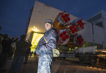 A police officer guards the Soyuz TMA-14M spacecraft as it is transported from an assembling hangar to its launch pad at Baikonur cosmodrome