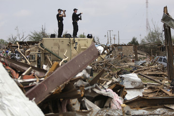 Secret Service agents scan the rubble as U.S. President Obama tours tornado damage in Moore, Oklahoma