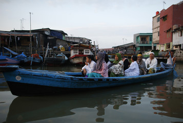 Muslims ride on a small boat on their way to attend a prayer session on Eid al-Fitr in Jakarta