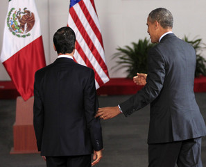 Mexico's President Pena Nieto walks with U.S. President Obama after he arrived to attend the North American Leaders' Summit in Toluca