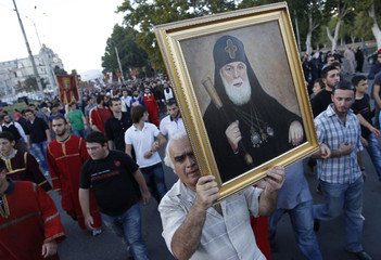 A believer shows off a portrait of Georgian Patriarch Ilia II during a procession against violence ahead of the parliamentary election in Tbilisi