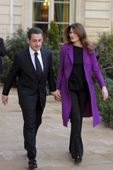 France's President Sarkozy and First Lady Carla walk to greet Ivory Coast First Lady Dominique Ouattara at the Elysee Palace in Paris