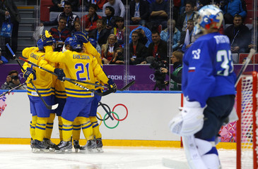 Sweden's Sedin is surrounded by his linemates celebrating his goal as Slovenia's goalie Kristan looks on during the third period of their men's quarter-finals ice hockey game at the 2014 Sochi Winter Olympic Games
