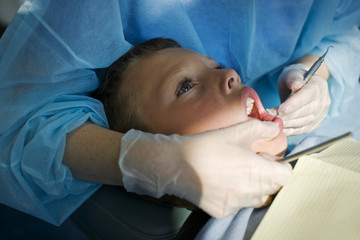 Boy getting teeth examined by the dentist