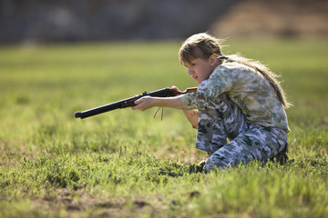 Young girl wearing camouflage clothing aiming a shotgun while crouching in a field. f