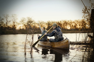 Portrait of a young adult man and his wife sitting in a canoe wearing camouflage attire on a lake.