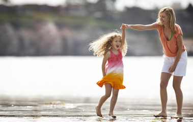 Mother helps her daughter spin around as they play on a beach at low tide.