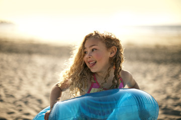 Young girl playing with an inflatable ring on the sand at the beach.