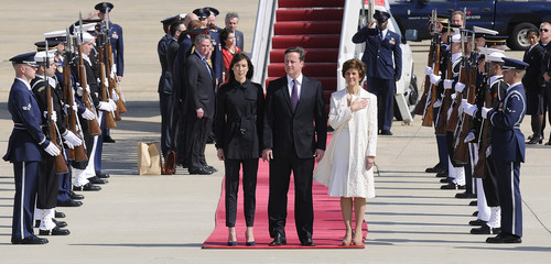 Cameron and his wife stand on the red carpet with Marshall for the playing of their national anthems during their arrival to begin his official visit to the U.S. at Andrews Air Force Base, Maryland
