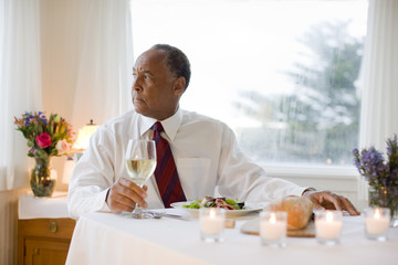 Man sitting at table with glass of wine
