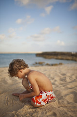 Young boy drawing a tic tac toe grid in the sand on a beach.