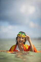 Smiling young girl playing in the water at a tropical beach.