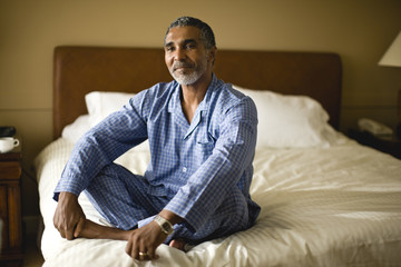 Man sitting cross legged on a bed.