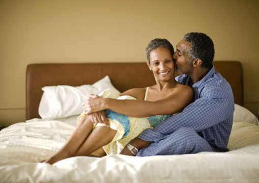 Couple kissing on their hotel bed.