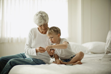 Mature woman in her pajamas sits on a bed with her young grandson and shows him a cell phone.