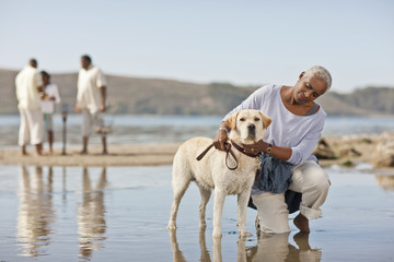 Mature woman kneeling next to a dog on a beach at low tide.