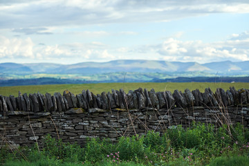 old dry stone wall in welsh countryside, mountains in background