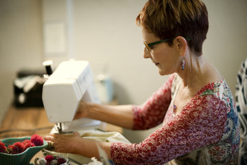 Middle aged woman using a sewing machine.