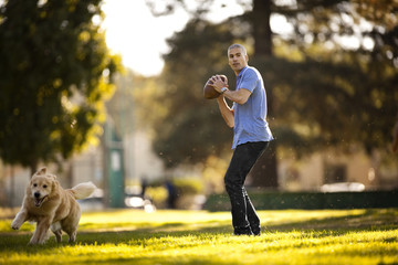 Mature man preparing to throw a football while in the park with his dog.