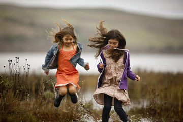 Two girls smile as they jump and splash in the waters of a marsh.