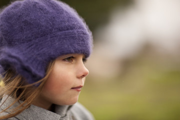 Young girl in a knit hat looks away as she poses for a portrait.