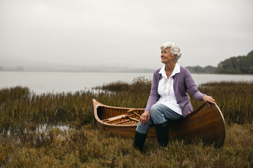 Mature woman smiles and looks away as she poses for a portrait while sitting on the gunwale of a wooden canoe pulled up on a lakeshore.