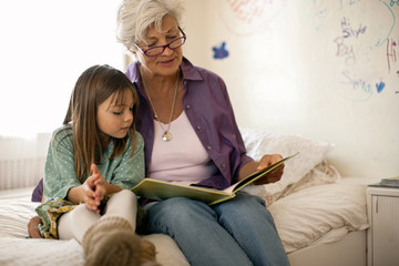 Grandmother reads a book with her young granddaughter as they sit together on a bed.