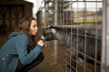 Teenage girl petting a goat.