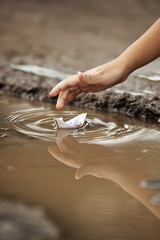 Child playing with paper boat in a puddle.