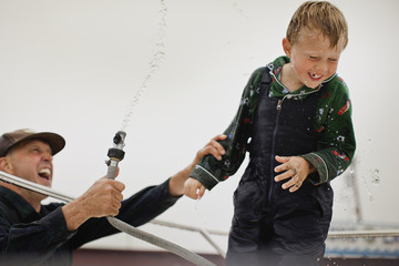 Mature man squirts his young son with garden hose.