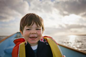 Little boy having fun sitting on rowboat.