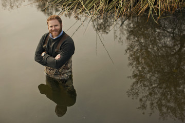 Portrait of a smiling mid adult man standing waist deep in a lake.