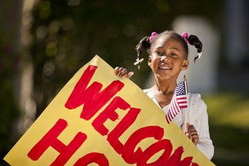 Young girl holding an American flag and a welcome home sign.