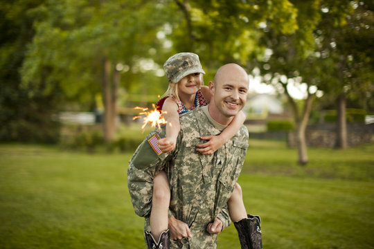 Smiling male soldier piggy-backing his young daughter in their back yard.