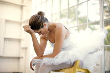 Mid adult ballerina sitting with her head in her hands.