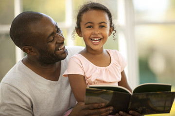 Smiling father and daughter reading a book together.