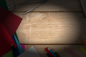 Schreibtisch mit Anspitzer, Zirkel, Tonpapier und Buntstiften von oben auf holz