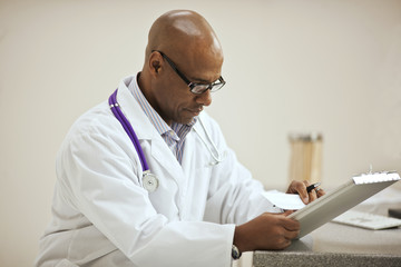 Focused male doctor taking notes on a clipboard inside his office.