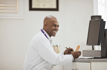 Laughing male doctor holding a box of medication inside his office.