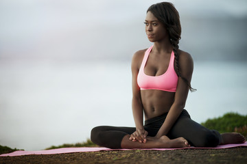 Young woman practicing yoga on a beach.