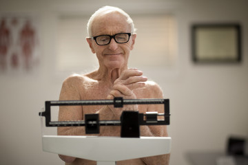 Senior man weighing himself on scales in a doctor's office.