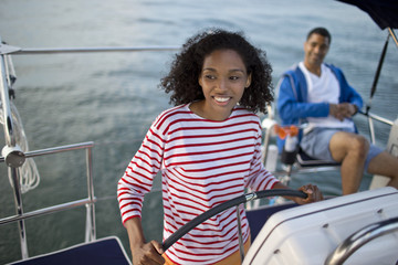 Smiling young woman steering a boat.